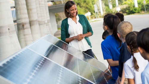 African American teacher in front of solar panels talking with students